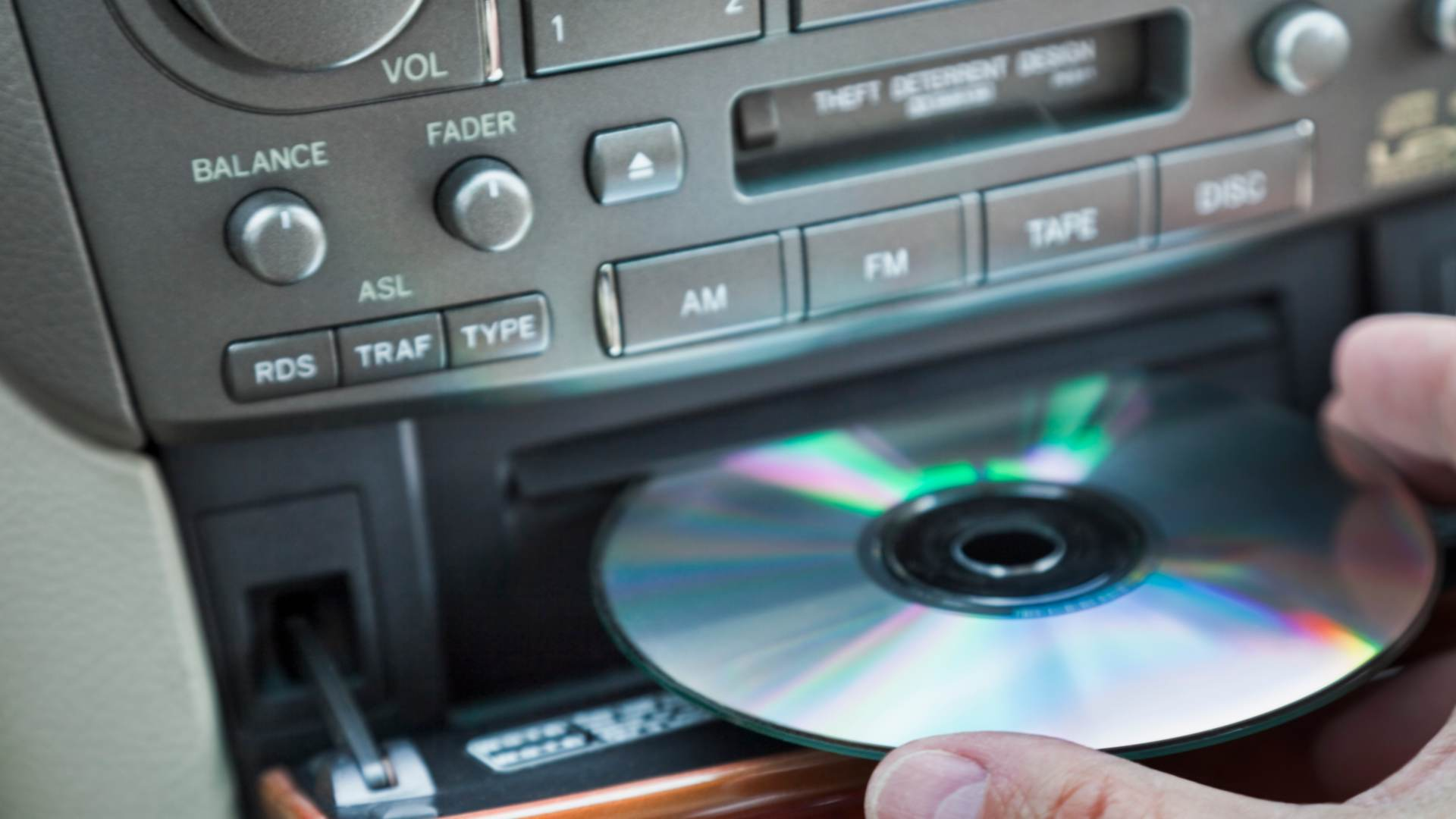A person inserting a CD into car CD player